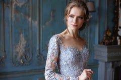 Ung blond brudkvinna i ett ljus - blå bröllopsklänning Royaltyfri Fotografi