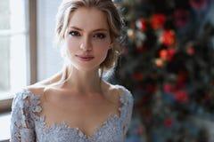 Ung blond brudkvinna i ett ljus - blå bröllopsklänning Arkivfoto