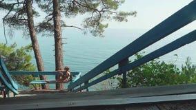 Ung blond caucasian hippieflicka på träskeppsdocka på blå havsbakgrund stock video