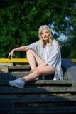 Ung blond flicka i mousserande hattsammanträde på trappa Royaltyfri Foto