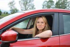 Ung blond flicka i röd bil som förlöjligar på något royaltyfri bild