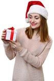 Ung blond flicka som hatten för santa ` s med gåvaasken Arkivbild