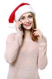 Ung blond flicka som hatten för santa ` s med telefonen Royaltyfria Bilder