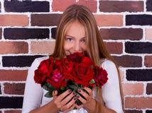 Ung blond flicka som luktar rosorna och ser kameran Fotografering för Bildbyråer