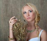 Ung blond flicka som poserar i slaviska etniska smycken och med en bukett av torkade förgyllda blommor Royaltyfri Foto