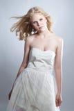 Ung blond flicka som poserar i studio i den vita klänningen royaltyfri bild