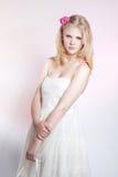 Ung blond flicka som poserar i studio i den vita klänningen arkivbild