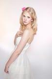 Ung blond flicka som poserar i studio i vitklänning arkivfoto