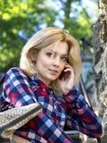 Ung blond flicka som talar på telefonen Arkivbild