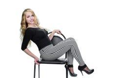 Ung blond flickaidrottskvinna som poserar på stol royaltyfri bild