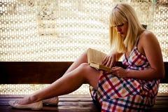 Ung blond flickaläsning royaltyfri foto