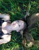 Ung blond kvinna för stående som lägger i gräset med långt hår och blåa ögon som ser upp lämnade med fridsamt uttryck arkivbild