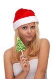 Ung blond kvinna i den santa hatten med godisen Arkivbild