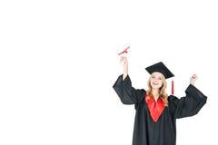 Ung blond kvinna, i diplom och att triumfera för avläggande av examenkappa hållande Royaltyfri Foto