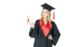 Ung blond kvinna i hållande diplom för akademikermössa och se kameran Arkivbild