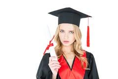 Ung blond kvinna i hållande diplom för akademikermössa och se kameran Royaltyfria Bilder