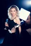 Ung blond kvinna i hållande vinexponeringsglas för svart klänning och se kameran Royaltyfri Foto