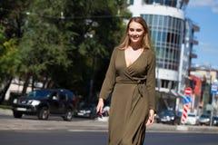 Ung blond kvinna i klänning som går i sommargata fotografering för bildbyråer
