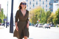 Ung blond kvinna i klänning som går i sommargata royaltyfria bilder