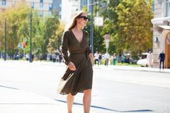 Ung blond kvinna i klänning som går i sommargata arkivfoto