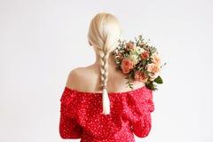 Ung blond kvinna i mammajeans och bukett f?r innehav f?r sk?rd?verkantskjorta av tulpan royaltyfri bild