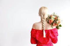 Ung blond kvinna i mammajeans och bukett f?r innehav f?r sk?rd?verkantskjorta av tulpan royaltyfri fotografi