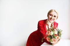 Ung blond kvinna i mammajeans och bukett f?r innehav f?r sk?rd?verkantskjorta av tulpan arkivbild