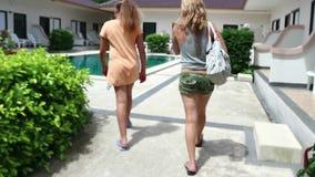 Ung blond kvinna med dottern som promenerar en aveny under palmträd till pölen stock video