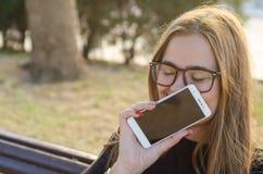 Ung blond kvinna med exponeringsglas som rymmer det mobilt och skratta arkivfoton