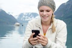 Ung blond kvinna med henne Smartphone i handen Fotografering för Bildbyråer