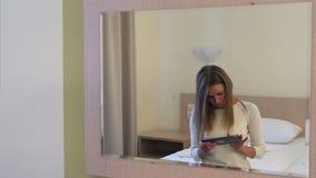 Ung blond kvinna som använder minnestavlasammanträde på sängen i hotellrum stock video