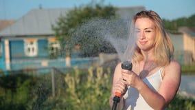 Ung blond kvinna som bevattnar en trädgård