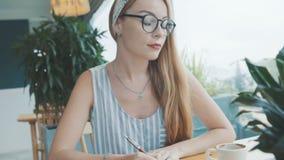Ung blond kvinna som dagdrömmer och skriver i hennes tidskrift, dagbok Kvinnlign skriver i anteckningsbok i kafé arkivfilmer