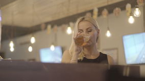 Ung blond kvinna som dricker ett exponeringsglas av öl på en stång arkivfilmer