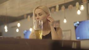 Ung blond kvinna som dricker ett exponeringsglas av öl på en stång lager videofilmer