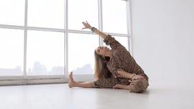 Ung blond kvinna som gör yoga i studio på en solig morgon stock video
