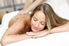 Ung blond kvinna som har massage och ler i brunnsorten royaltyfria foton