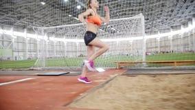 Ung blond kvinna som kör och utför ett längdhopp i sportarenan stock video