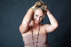 Ung blond kvinna som skjuter upp hennes hår Arkivbild