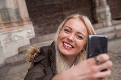 Ung blond kvinna som tar en selfie Arkivbild