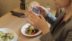 Ung blond kvinna som tar fotoet av smaklig sallad med smartphonen i restaurang arkivfilmer