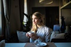 Ung blond kvinna som tycker om kaffetid i kafé Royaltyfri Foto