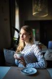 Ung blond kvinna som tycker om kaffetid i kafé Royaltyfria Bilder