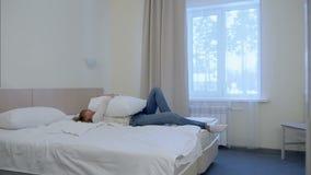 Ung blond kvinnabanhoppning in i vit hotellsäng stock video