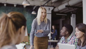 Ung blond kvinnachef som talar med laget för blandat lopp Affärskvinna som ger riktning till kollegor på det moderna kontoret Arkivbilder