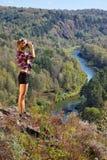Ung blond kvinnaturist på en klippa som ser till och med binocula royaltyfria bilder