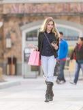 Ung blond kvinnlig shopping med rosa och röda påsar som rymmer en mobiltelefon arkivbild