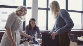 Ung blond lagledare som går till och med modernt kontors- och kontrollarbete av anställd Kvinnlign ser tygexemplen arkivfilmer