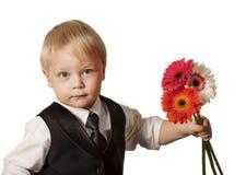 Ung blond man in med bukettblommor. Royaltyfri Fotografi