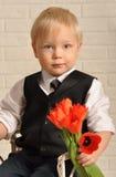 Ung blond man in med bukettblommor. Royaltyfri Foto